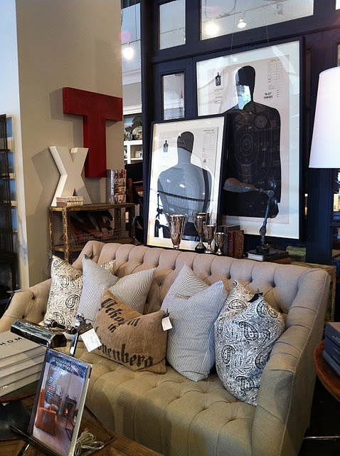 Beautiful tufted couch. Love the framed target practice papers.. Cindy, you should have Jas get one for you!!