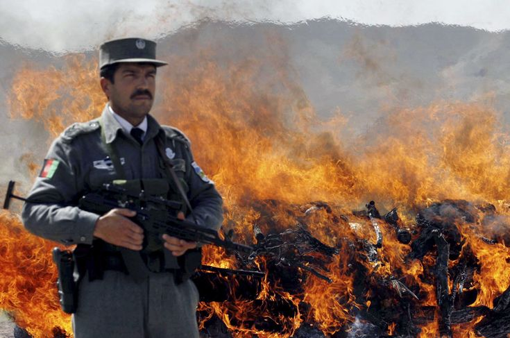An Afghan security officer stands guard as flames rise during a drug burning event on the outskirts of the city in Herat province, west of Kabul, Afghanistan, Wednesday, March 18, 2009. Over 2,000 kilograms of narcotics, composed of heroin, opium and hashish, were burnt along with some bottles of alcoholic drinks. (AP Photo/Fraidoon Pooyaa) #