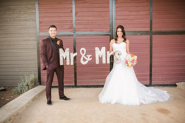 Giracci farms outdoor rustic wedding bride a line strapless gown with a sweetheart neckline and lace detail with groom burgundy shawl lapel tuxedo with black dress shirt and black faux leather bow tie with floral boutonniere holding mr and mrs sign
