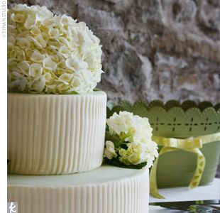 """two-tiered cake covered in antique white fondant that had a corrugated texture. The tops of the tiers were frosted in pale green and topped with fresh hydrangeas. """"It was lemon-flavored and absolutely delicious!"""" the bride reports."""