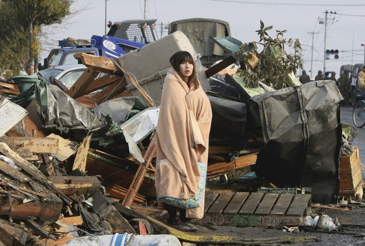 A woman looks at the damage caused by a tsunami and an earthquake in Ishimaki City, Miyagi Prefecture, on March 13, 2011.