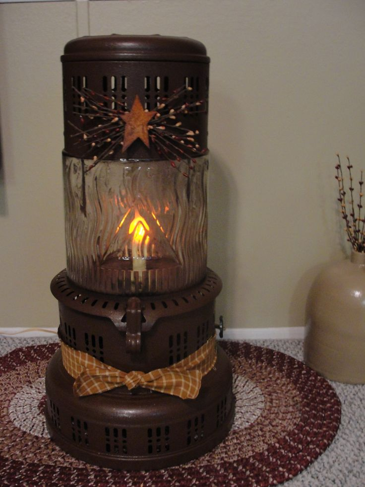 I have a love for decorating with antiques this glass kerosene heater I painted and added tin star with pip and some homespn tied around it then added a orange flicker electric candle light inside great for prim decor