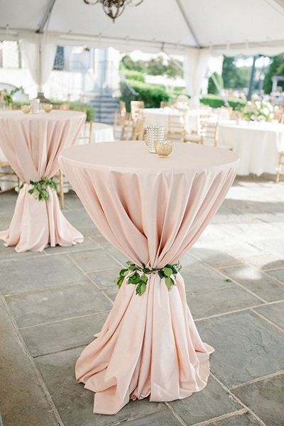 Don't just drape your cocktail tables in linen and call it a day; cinch it with a tie of lush greenery — or twine or fabric if you wish — to give a little pizazz to its silhouette. From #BridalGuide #WeddingReception #WeddingDecor #WeddingCocktailTables
