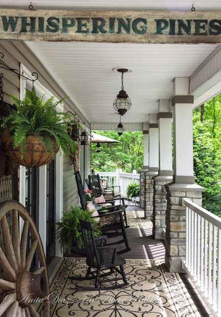 A consistent color scheme with a heavy dose of patterns mixed in helps to give the entire porch a more cohesive feel. White accents, including the paneled ceiling and fencing, help brighten the space up.