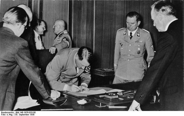 Adolf Hitler signing the Munich Agreement, Germany, 30 Sep 1938; note Joachim von RIbbentrop, Benito Mussolini, and Julius Schaub in background