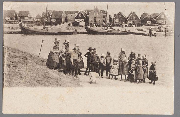 Een grote groep kinderen in Marker dracht poseren met op de achtergrond de Marker haven met twee botters en de houten huizen van de Havenbuurt. 1895-1905 #NoordHolland #Marken