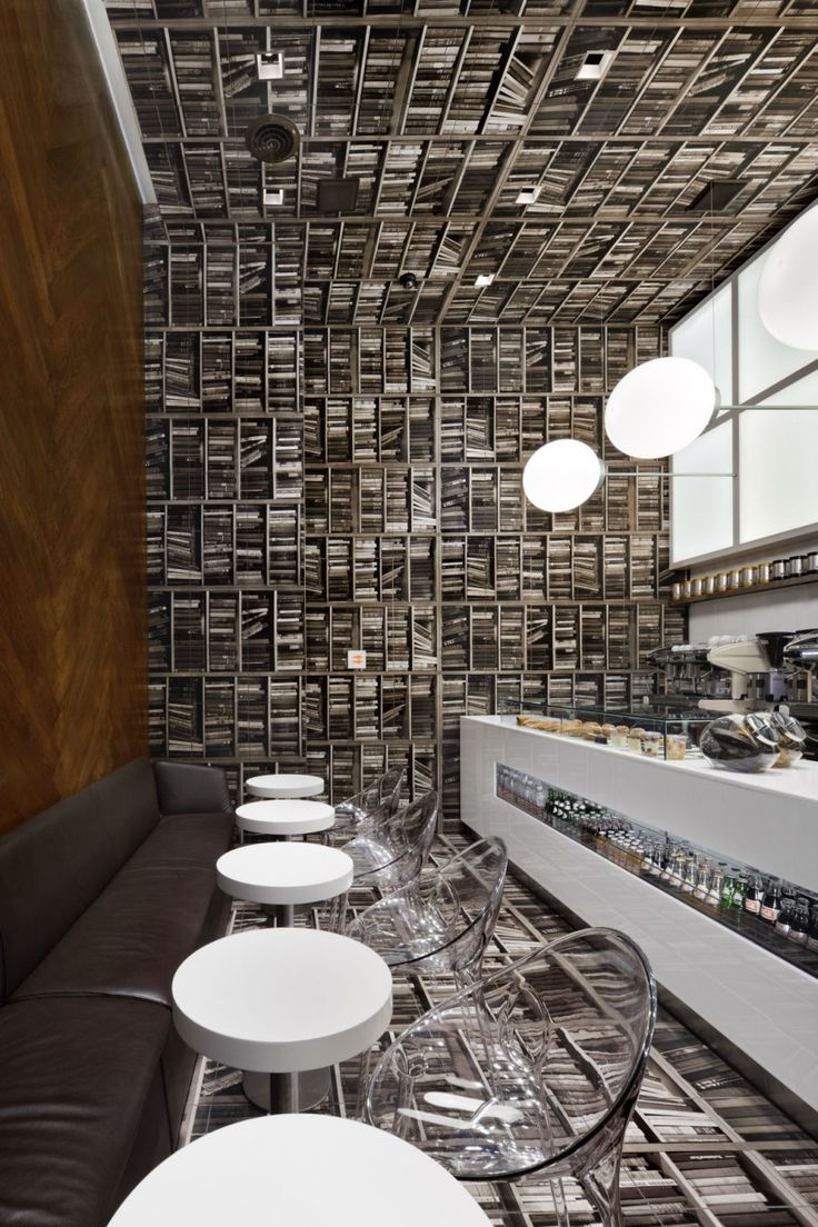 D'espresso Cafe Interior by Nema Workshop - Take a library and turn it SIDEWAYS. The booklined shelves become the floor and ceilings and wood floor ends up on the walls!