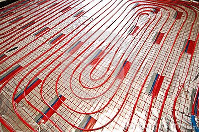 Red, plastic pipes of floor heating, with reflective foil. House building and renovation stage.