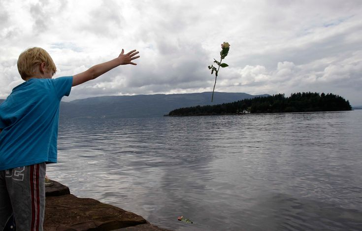 A young boy throws a rose into the lake opposite Utoya in remembrance of victims.
