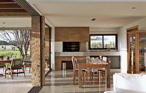 A sala de jantar fica junto à área da churrasqueira e é integrada à varanda pelas portas de vidro que correm em trilhos de alumínio para as laterais. Projeto do escritório Seferin