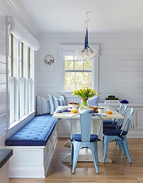 This well appointed blue and white beach bungalow dining space features a built in white L-shaped banquette sat under windows dressed in a white roman shades framed by shiplap walls and topped with blue tufted cushions.