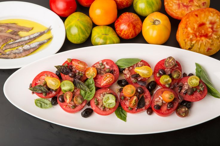 In the height of summer, a stellar but simple tomato salad is essential dinner party fare. This one has the distinct profile of a niçoise: Thick slices are arranged on a platter, then topped with a garlicky chopped olive vinaigrette and colorful halved cherry tomatoes. (Photo: Fred R. Conrad/The New York Times)
