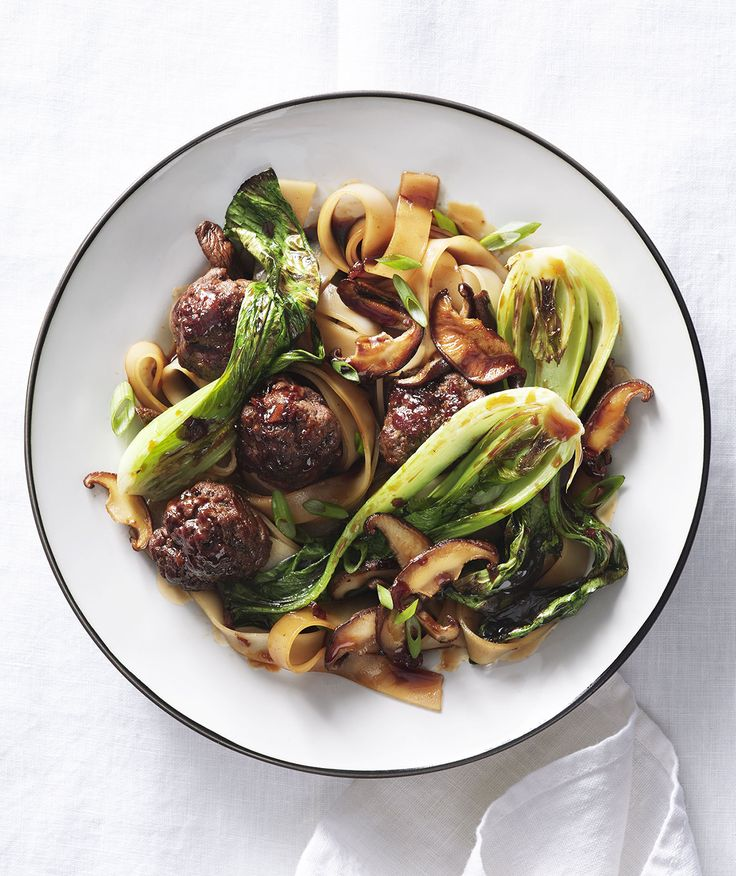 Rice Noodles With Meatballs, Mushrooms, and Bok Choy | This gluten-free noodle dish is deeply satisfying, thanks to a homemade sauce seasoned with soy sauce and fresh ginger.