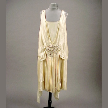 Worth Wedding Gown French, circa 1925 The sleeveless chemise of ivory charmeuse, with dropped waist defined by blousing of bodice, the bodice front decorated with long string of graduated pearls descending in V to large waist ornament of variously shaped and sized pearl elements, the V back embellished with a yoke of knotted silk cord sewn with pearl ornaments, the skirt front elaborated with two pleated panels descending from front pearl ornament and looping under hem