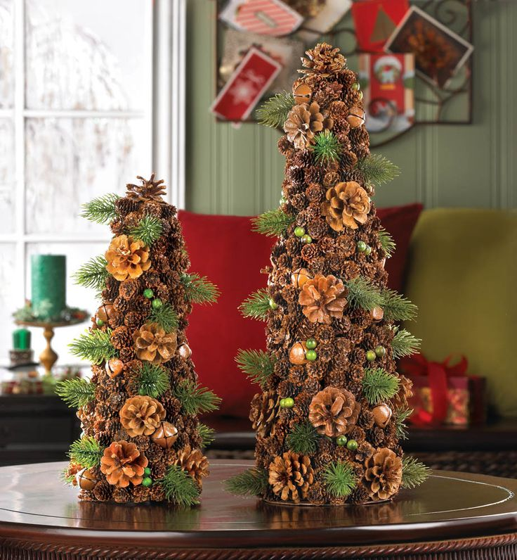 The perfect organic accent to dress up your home for the holidays! Pine cones of varying sizes stack up to create this large tree shape, spruced up with pine sprigs, green berries and jingle bells. It