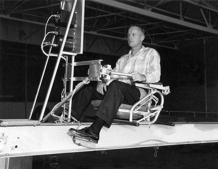 Closeup of research pilot Neil Armstrong operating the Iron Cross Altitude Simulator reaction controls, 8 October 1956, public domain via Wikimedia Commons