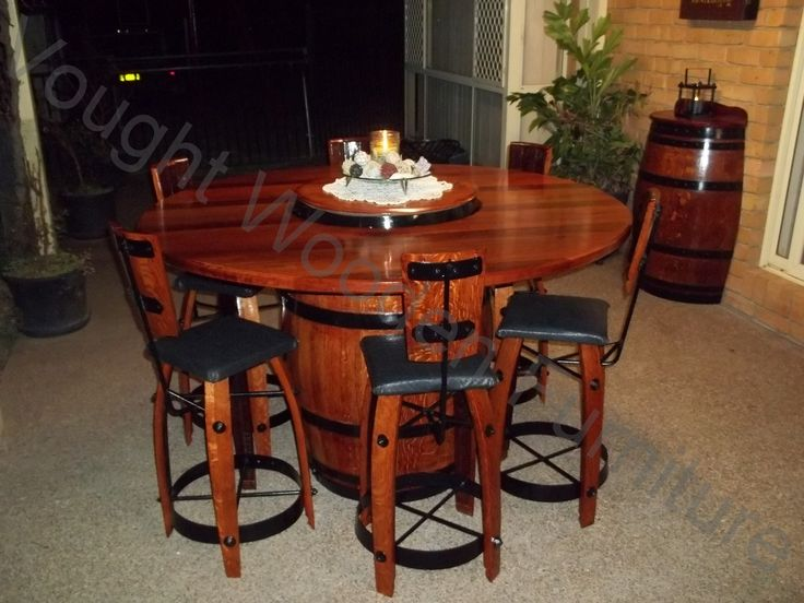 wine barrel bistro table with 6 chairs night time photo table has a lazy susan with it which is made from the top piece of a wine barrel table top is arched table top wine cellar furniture