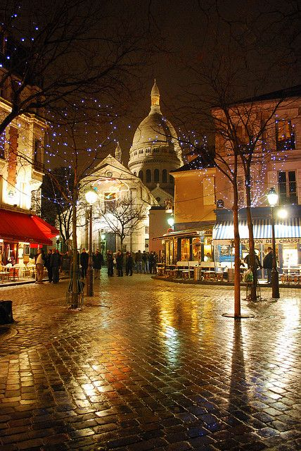 Colorful lights reflect on the wet pavement of Place de Tartre in Montmarte, Paris. In the background, the dome of Sacre-Coeur can be seen.