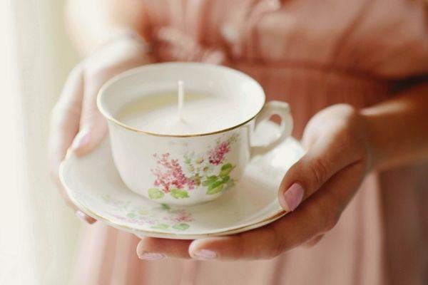 Une tasse en porcelaine ancienne utilisée comme un bougeoir