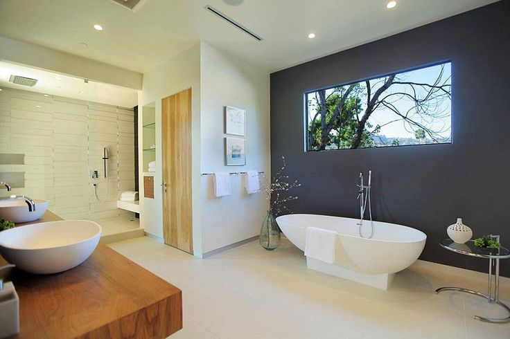 Bagno moderno di grandi dimensioni dotato di doccia e vasca da bagno e una grande finestra che fornisce luce naturale in abbondanza