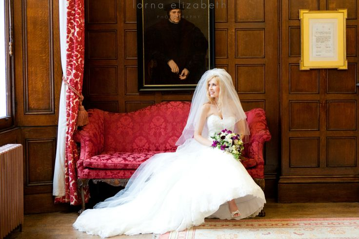 A romantic shoot of the bride on the red sofa in the Queen's Room