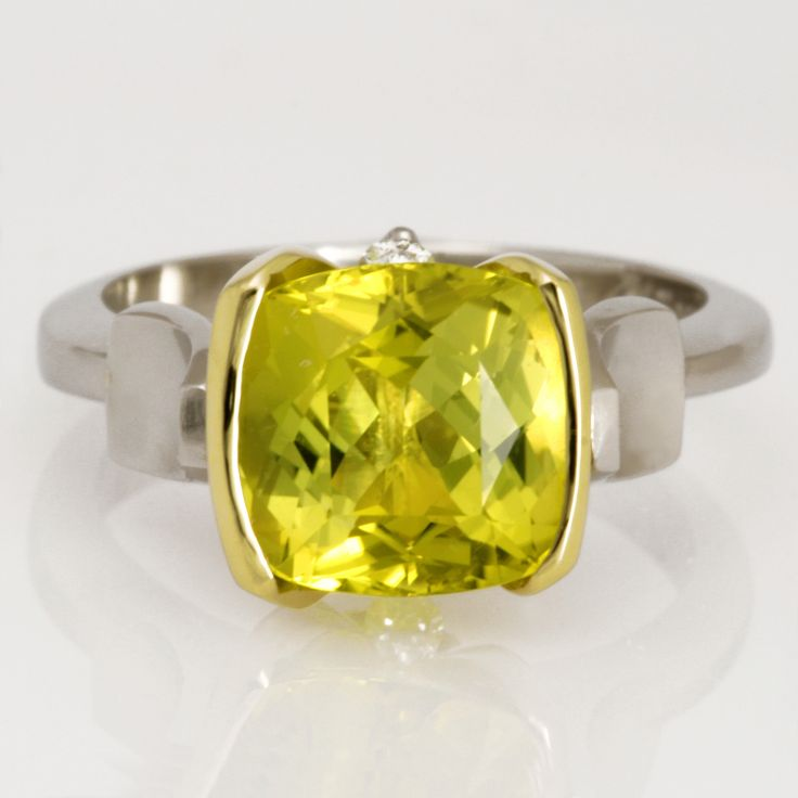 Ladies platinum ring with an asymmetrical setting featuring a cushion cut yellow green tourmaline and diamonds