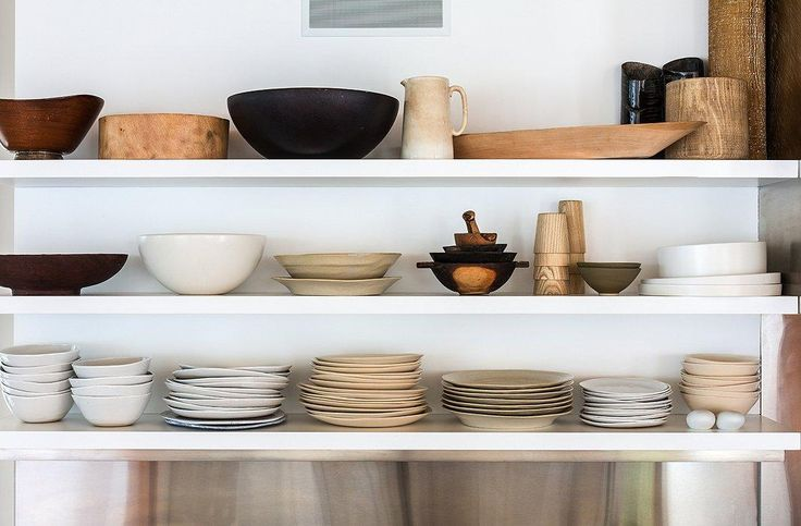 The house's airiness extends into the kitchen, where open shelving holds Kelly's collection of dishes and serveware.