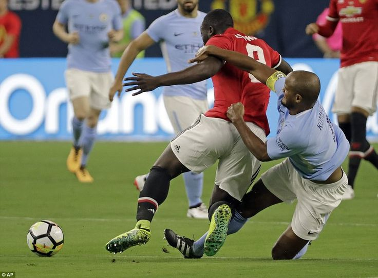 Lukaku goes to ground under the challenge of his fellow Belgian, Manchester City'sVincent Kompany