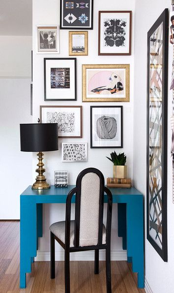 Contemporary Hollywood Regency Work Space: A collection of artwork hangs above a blue desk .