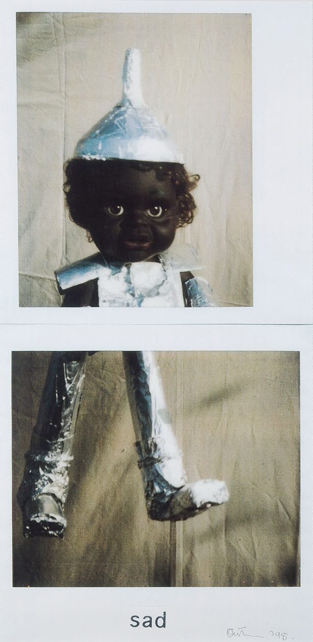Destiny Deacon  (Australia 1957– )    Language group  Kuku / Erub, East Cape region / Torres Strait region  Title  Sad, from the series Oz  Year  1998  Media  Photograph  Medium  Bubble jet print from Polaroid photograph