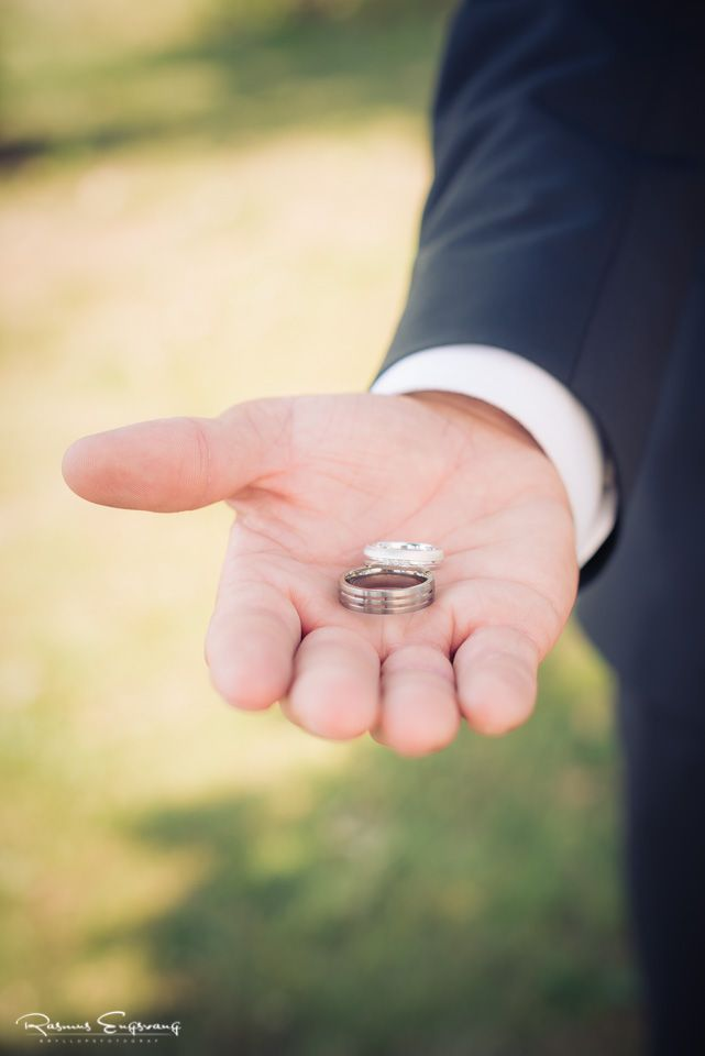 Her viser gommen parrets flotte vielsesringe frem i sine hænder.
