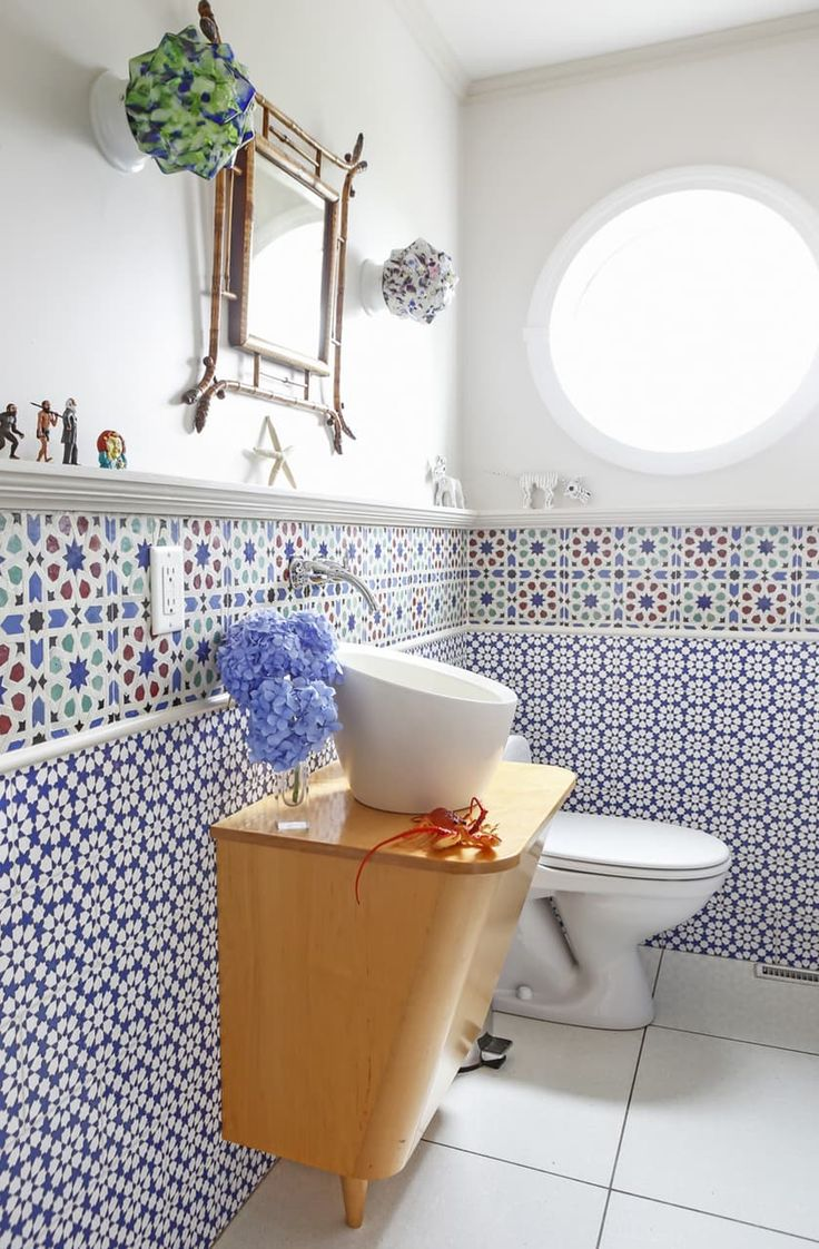 This bathroom in a cottage by the sea certainly as the tropical vibes down. With the round window, to the starfish, to the tropical tile on the walls this bathroom has it all. Unique glass sconces and the fun shaped bowl sink put it over the top!