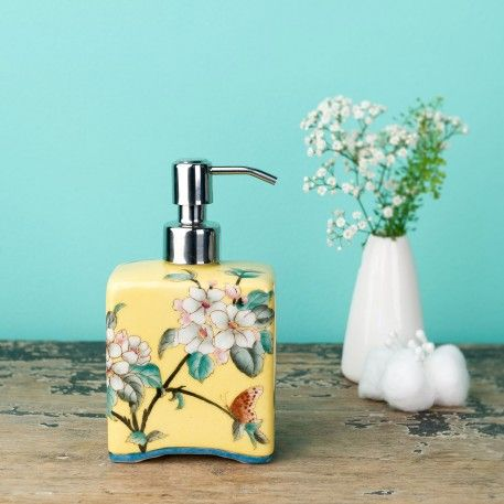 A yellow ceramic soap dispenser or hand-cream dispenser. Pretty for a kitchen or bathroom, this one is decorated with flowers.The perfect house-warming gift.