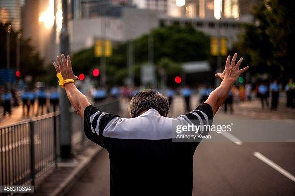 News Photo : A man raise his hands outside of Hong Kong...