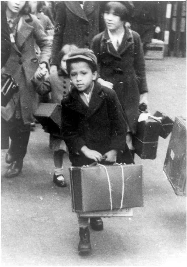 """A small black boy carrying his luggage as he left London  for the country with a party of other evacuees on 5 july 1940""."