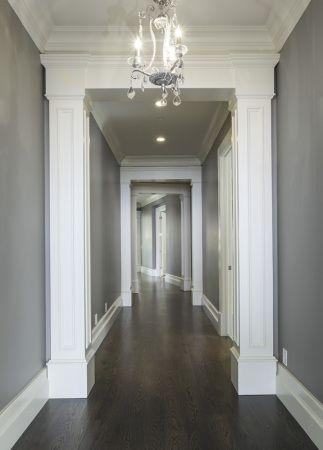 Lane Myers Construction Custom Home Builder Loeffler Residence Draper Utah Versailles Inspired Hallway Hardwood Floors Dark Gray Walls White Trim