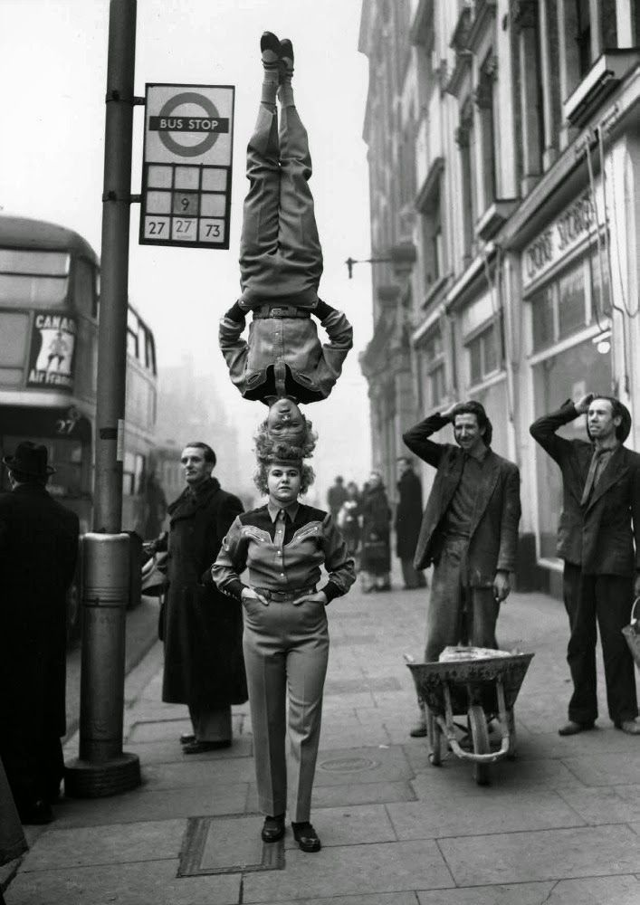 Two members of the Bertram Mills Circus walk head-to-head at Hammersmith Broadway in London. 1953