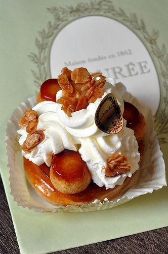 The St. Honoré cake is named for the French patron saint of bakers and pastry chefs, Saint Honoré or Honoratus (d. 600 AD), bishop of Amiens. It is a circle of puff pastry base with a ring of pâte à choux piped on the outer edge. After the base is baked small cream puffs are dipped in caramelized sugar and attached side by side on top of the circle of the pâte à choux. This base is traditionally filled with crème chiboust and finished with whipped cream using a special St. Honoré piping tip.