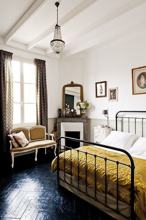 Romantic bedroom with crystal chandelier, black parquet flooring, wrought iron bed frame, Parisian-inspired love seat and gold French mirror leaning on the fireplace.