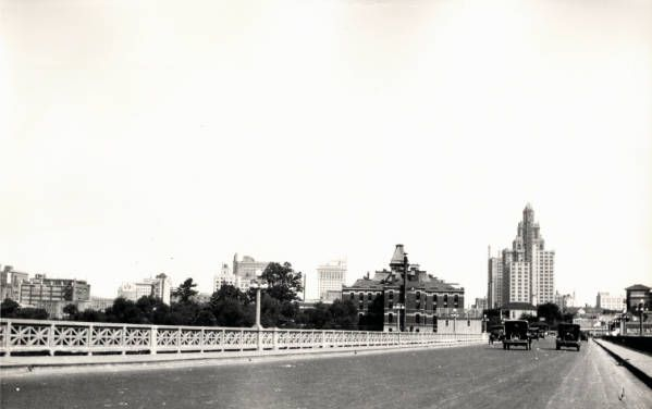 """Houston skyline from a street level bridge. 1927. A view of the downtown Houston skyline looking east from an unidentified bridge. The bridge led into the downtown district between Capitol Avenue and Rusk Avenue. The Esperson Building is the tallest building seen in the photograph. George Fuermann """"Texas and Houston"""" Collection, 1836-2001. Special Collections, University of Houston Libraries (Public Domain)."""