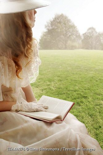 Trevillion Images - vintage-woman-reading-book-in-field