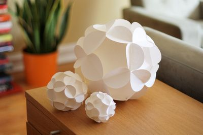 Paper ball tutorial - These are made from 12 slotted flower shapes that fit together to form a sphere. No adhesive needed; the only ingredient is paper.