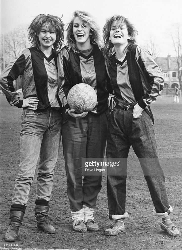 Portrait of pop band 'Bananarama', (L-R) Keren Woodward, Sarah Dallin and Siobhan Fahey, wearing football shirts and standing in a field, March 16th 1983.