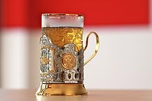 "The podstakannik (Russian: подстака́нник, literally ""thing under the glass""), or tea glass holder, is a holder with a handle, most commonly made of metal that holds a drinking glass (stakan). Their primary purpose is to be able to hold a very hot glass of tea, which is usually consumed right after it is brewed. The stability of the glass on the table is also significantly improved. It is a traditional way of serving and drinking tea in Russia, Ukraine, Belarus, and other post-Soviet…"
