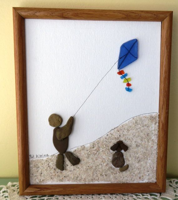 This original framed art picture was created from Lake Michigan beach pebbles, beach glass, sand and ink on canvas board. It is framed in a recycled oak frame. The picture features a boy flying his kite in the sand dunes while his dog looks on, The framed picture measures 11x9.