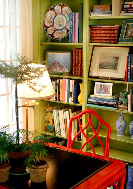 Meg Braff's green library gets lots of punches of Chinoiserie color from a red Chinoiserie desk and Chinese Chippendale chair, blue and white Chinese porcelain, green and yellow foo dogs, and an Imari porcelain plate.