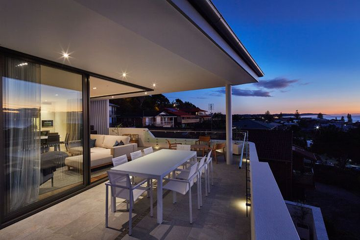 The balcony on this townhouse has been set up for outdoor dining, perfect for watching the sun set over the ocean.