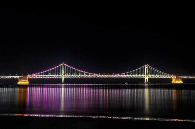 Gwangan Bridge In BUSAN: Stretching across Haeundae-gu and Suyeong-gu, the Gwangan Bridge is the longest bridge in Korea, offering over a 100,000 magnificent lighting effects at night to form one of Korea's finest after-dark scenes. What's more, a number of bars and restaurants are located along the bridge and provide a wide selection of dining options, ranging from authentic street food, casual meals and even fine dining.