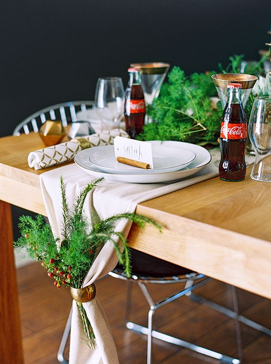 Cloth table runner with a napkin ring and greens. #cokestyle #holidays Thanks to our friends at Coca‐Cola.