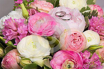 Trouwringen op boeket van witte en roze pioenen